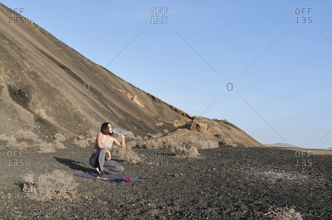 Fit young woman in sportswear drinking water after a workout session outside in extreme terrain