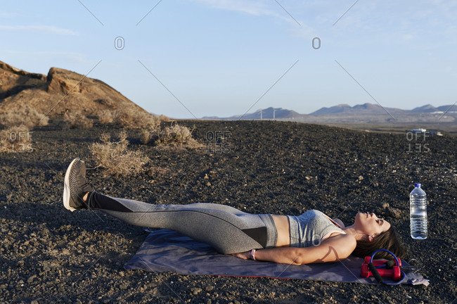 Fit young woman in sportswear doing leg raises during an outdoor workout in rocky terrain