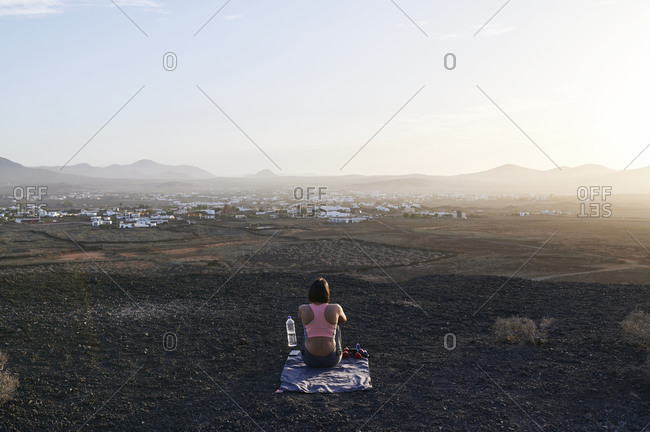 Rear view of a fit young woman in sportswear sitting on some rocky ground and watching the sunset after working out