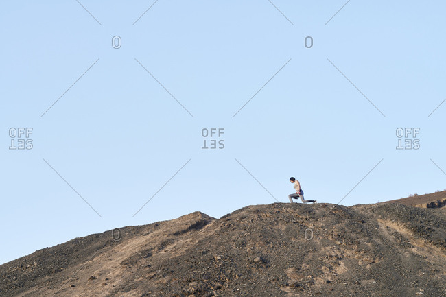 Fit young woman in sportswear doing lunges with dumbbells during an outdoor workout on a distant rocky hill