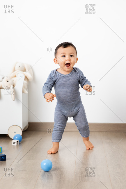 Cute toddlers making first steps with proud funny face
