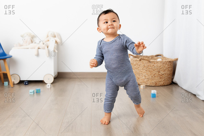 Cute toddler making first steps in playroom