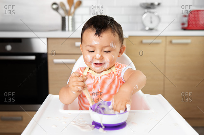 Cute messy baby eating yogurt with his hands