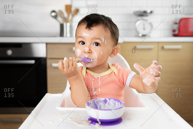 Messy baby in high chair eating yogurt with spoon