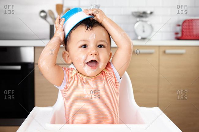 Funny baby with messy yogurt face holding bowl on top of head