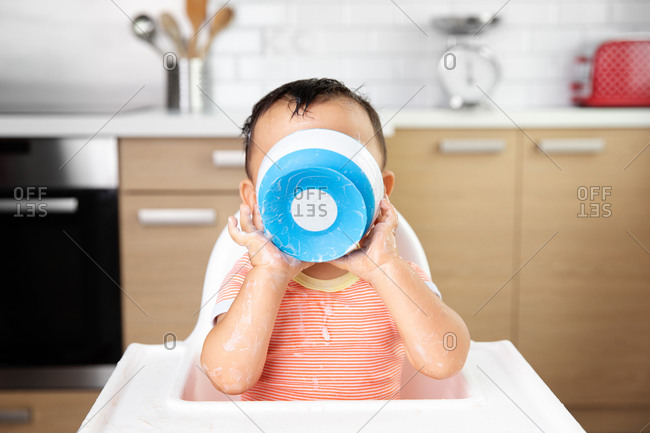 Messy baby in high chair holding bowl against face