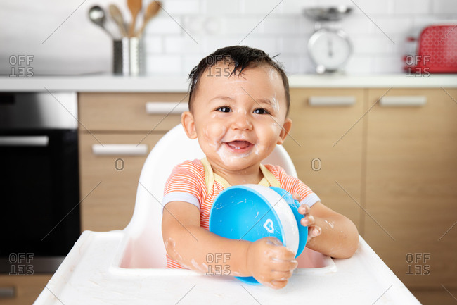 Happy baby with messy yogurt face holding empty bowl