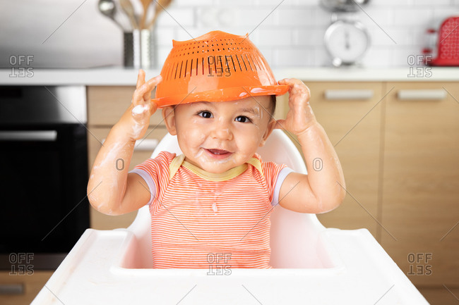 Funny messy baby holding colander on top of head