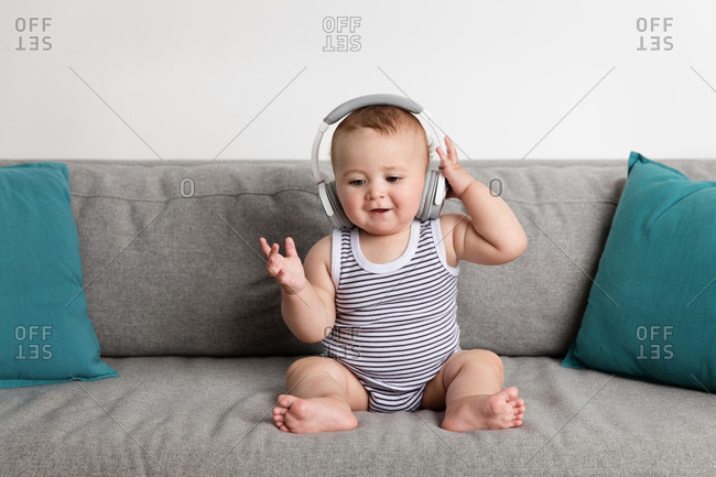 Smiling baby boy sitting on sofa listening to music with headphones