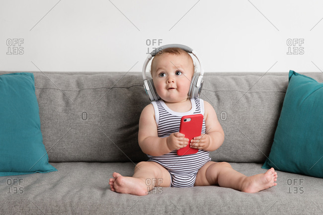 Cute baby boy sitting on sofa listening to music with headphones and smartphone