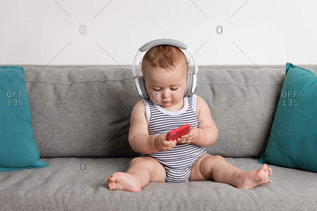 Cute baby boy sitting on sofa listening to music with headphones looking at smartphone