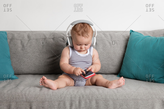 Cute baby boy sitting on sofa listening to music with headphones touching smartphone screen