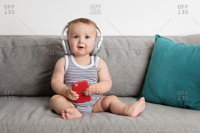 Baby boy sitting on sofa holding smartphone and listening to music with headphones