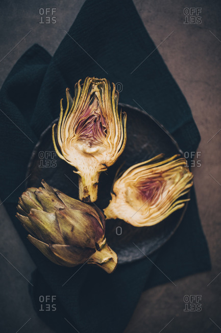 Two artichokes on dark plate viewed from above, one whole and one cut in half