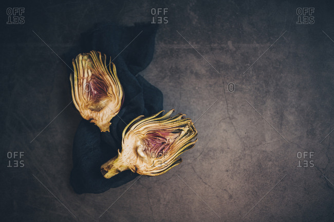 Two halves of a cut artichoke on black napkin, viewed from above