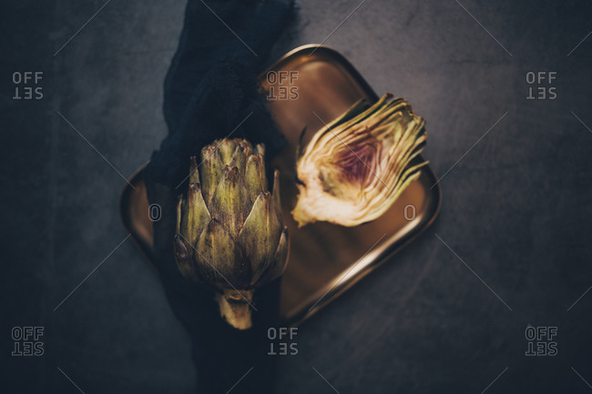 Whole and cut artichokes on a metal plate with linen black napkin viewed from above