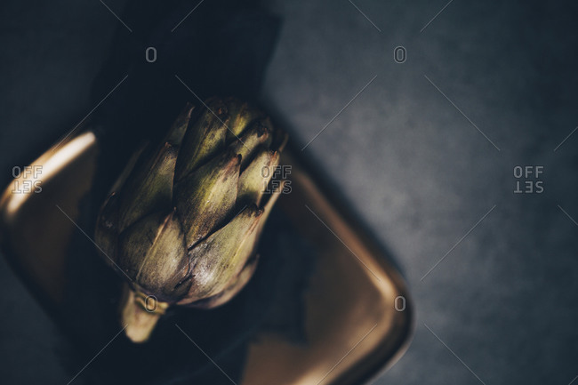 Close up of a whole artichoke on a metal plate with linen black napkin viewed from above