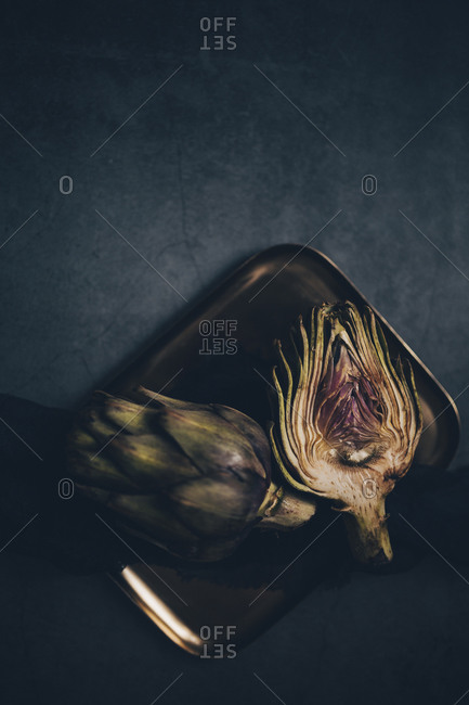 Overhead view of whole and cut artichokes on a metal plate with linen black napkin viewed from above