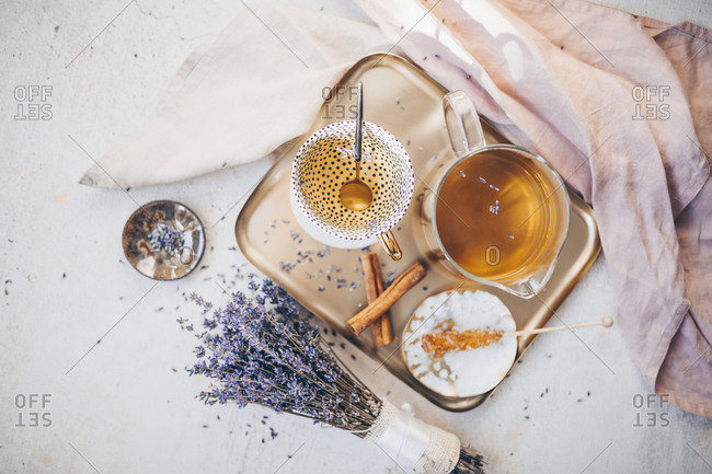Top view of a tea set on a tray served with lavender and cinnamon