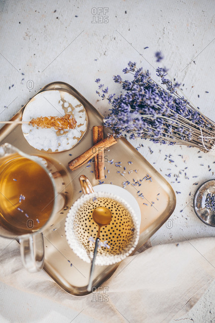 Overhead view of a tea set on a tray served with lavender and cinnamon
