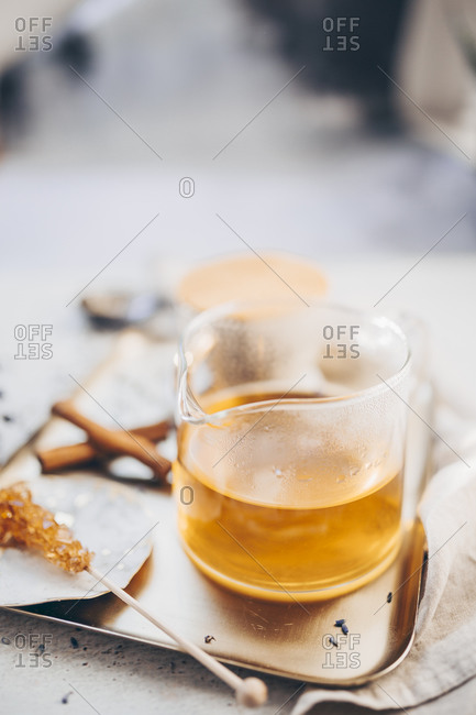 Front view of tea in a beaker on a tray served with sugar crystal stick and cinnamon