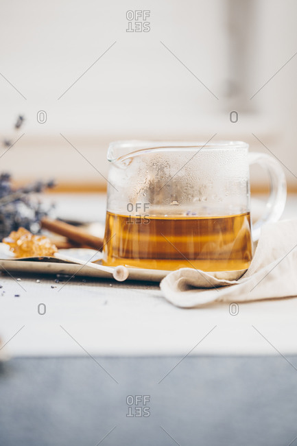 Close up of tea in a beaker on a tray served with lavender and cinnamon