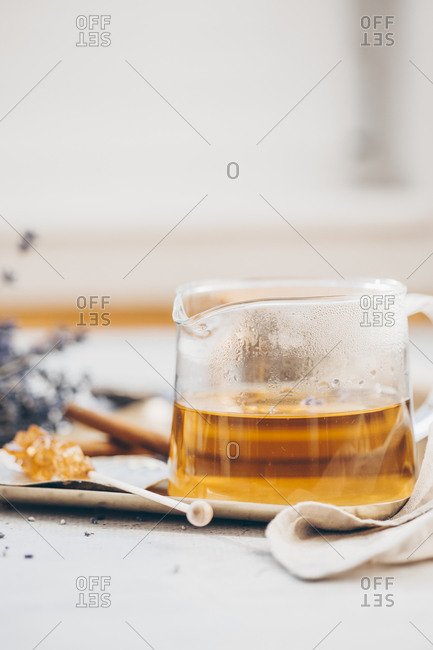 Tea in a beaker on a tray served with lavender and cinnamon