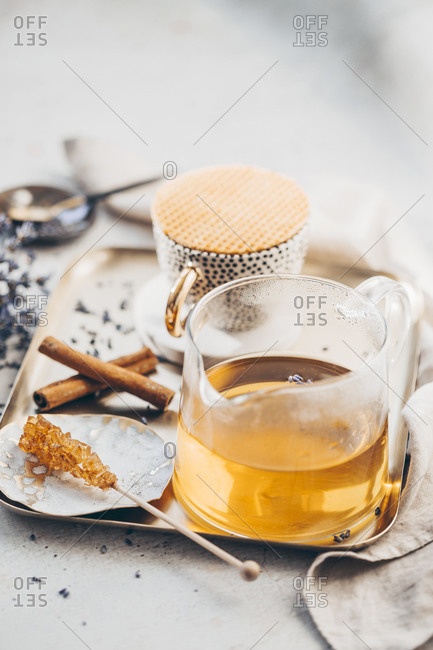 Front view of a tea in beaker on a tray served with lavender and cinnamon