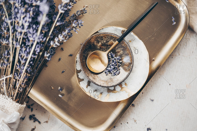 Top view of a sprig of lavender on a golden plate with spoon and dishes