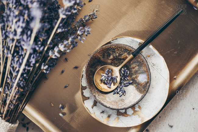 A sprig of lavender on a golden plate with spoon and dishes