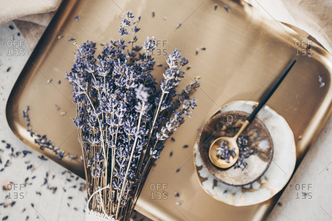 Overhead view of a sprig of lavender on a golden plate with spoon and dishes