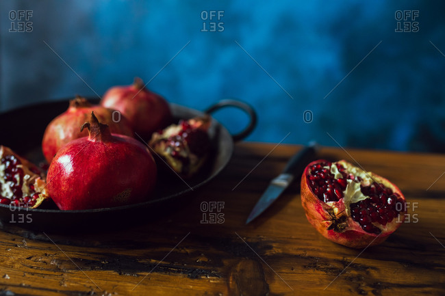 Pomegranate fruits on wooden table with blue background