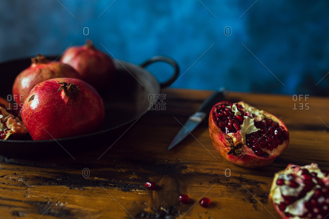 Pomegranate fruits on wooden table with knife with blue background