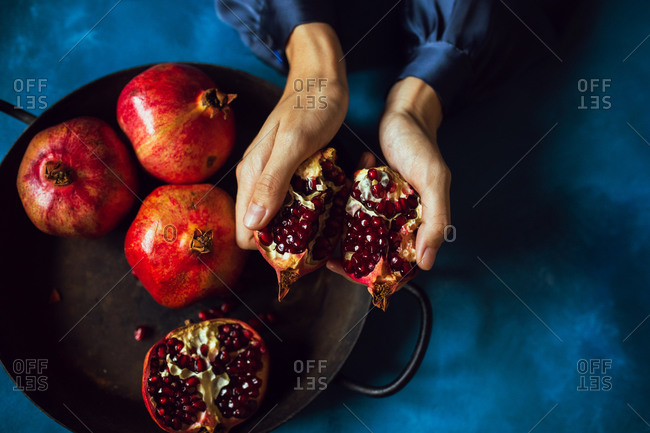 Woman's hands breaking opening a pomegranate fruit viewed from above