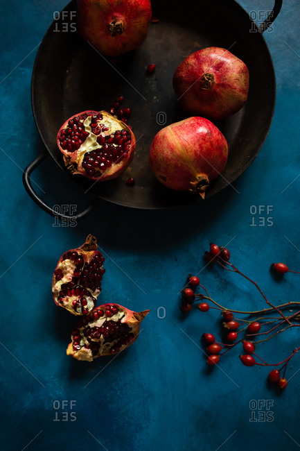 Overhead view of pomegranate fruits on blue background with rose hips