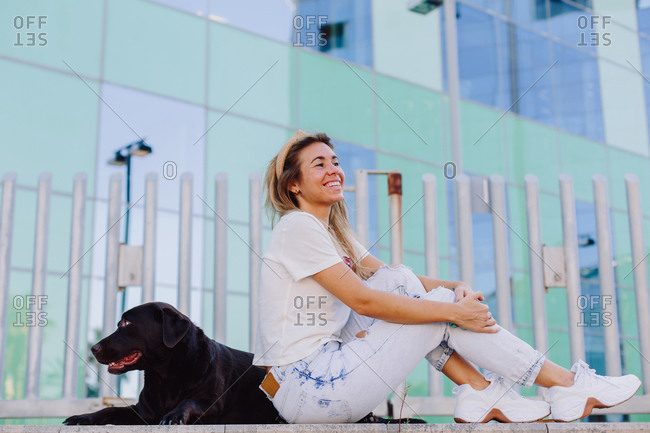 Side view of female in summer wear sitting on bench with obedient Labrador Retriever while relaxing during city stroll and looking away