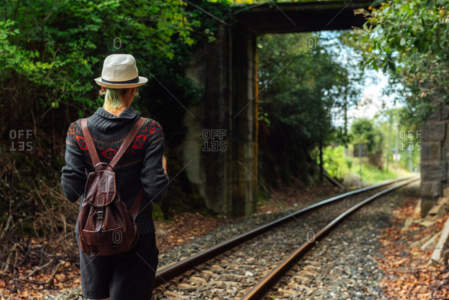 Back view of female traveler with backpack standing on rails in forest during summer adventure