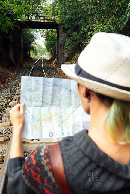 Back view of unrecognizable tourist standing in woods with paper map and finding route during vacation