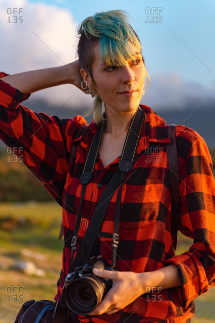 Side view of androgynous female traveler with professional photo camera standing on hill in mountainous area