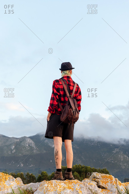 Back view low angle of carefree explorer standing on rocky hill in highlands and enjoying freedom with outstretched arms during adventure