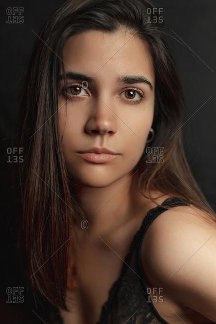 Serene slim female in black lace bra looking at camera on dark background in studio