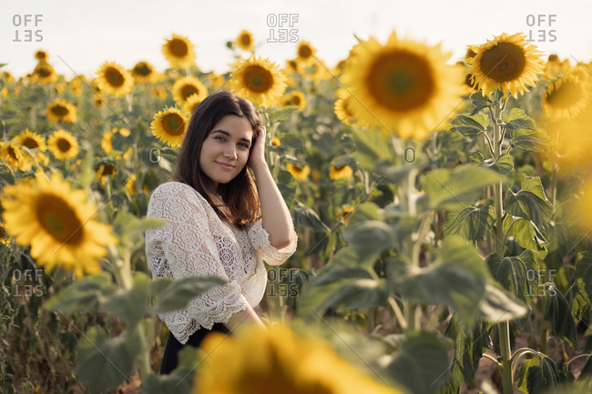 Peaceful female standing in meadow with blooming sunflowers and enjoying nature looking at camera