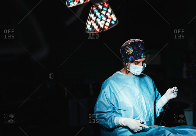 Side view of focused professional female surgeon with surgical tools and thread finishing operation of patient in operating theater