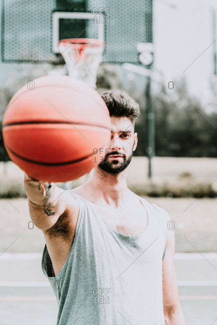 Confident young bearded player in sport shirt holding basketball ball and looking at camera while training alone on street playground