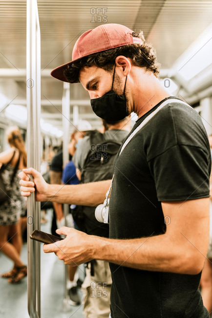 Side view of adult male passenger in casual outfit and black protective mask for coronavirus prevention browsing mobile phone during trip in subway train