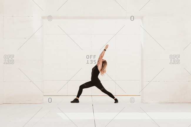 Full body side view of fit flexible female in black sportswear doing Crescent Lunge pose with arms raised while practicing yoga in light studio