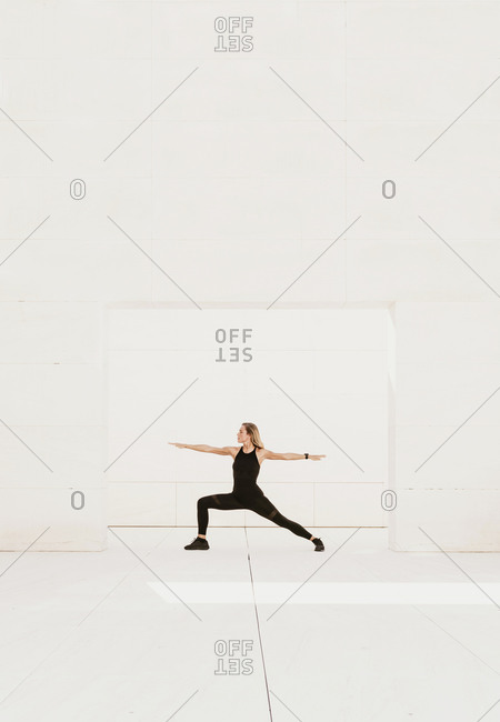 Full body side view of slim female in black sportswear performing balancing Warrior asana while practicing yoga in spacious light studio
