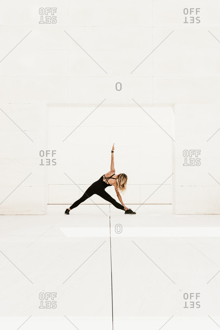 Full body side view of slim female in black sportswear performing balancing triangle pose while practicing yoga in spacious light studio