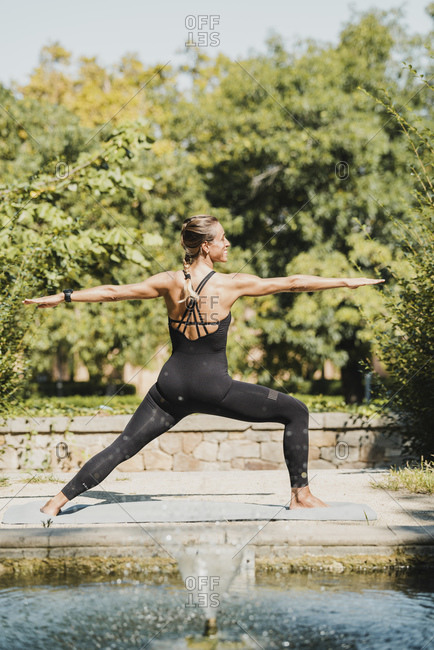 Back view of slim female in sportswear performing Tree pose with arms up while practicing warrior yoga near fountain in sunny summer park