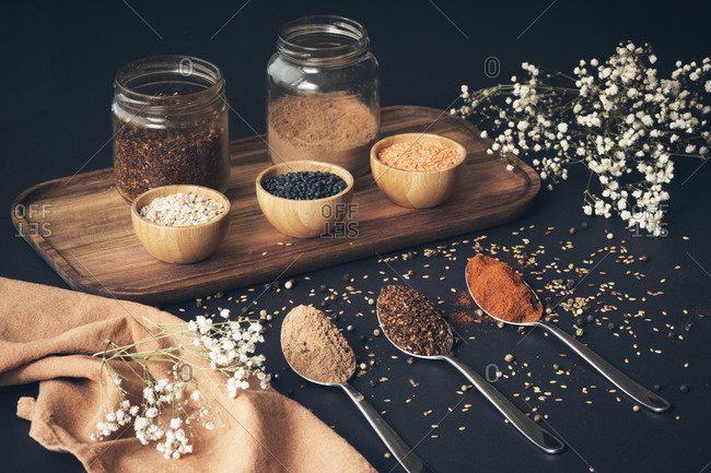 Top view of assorted grains in jars and aromatic spices in spoons arranged on wooden tray on black table